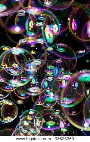 many soap bubbles flying on black background