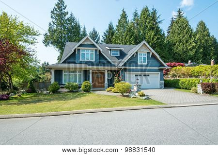 Luxury blue house with beautiful landscaping on a sunny day. Home exterior. poster