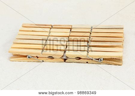 Several wooden clothespin taken closeup on white fabric background. poster