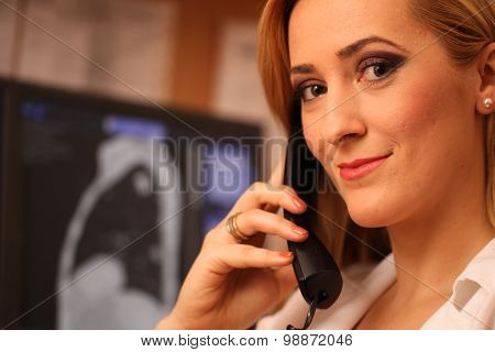 Portrait Of A Smiling Female Doctor Sitting At Work Desk
