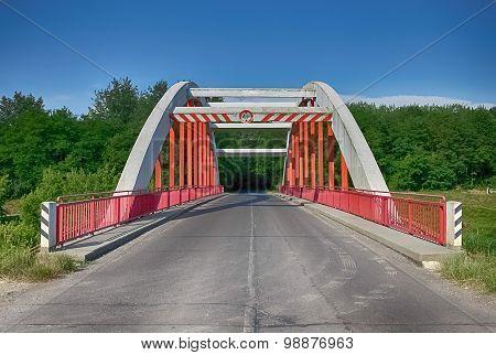 red bridge, asphalt, forest and blue sky