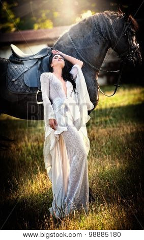 Fashionable lady with white bridal dress near brown horse in nature. Beautiful young woman