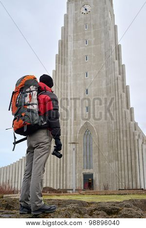 rear view of man standing in front of the Hallgrimskirkja cathedral in reykjavik iceland