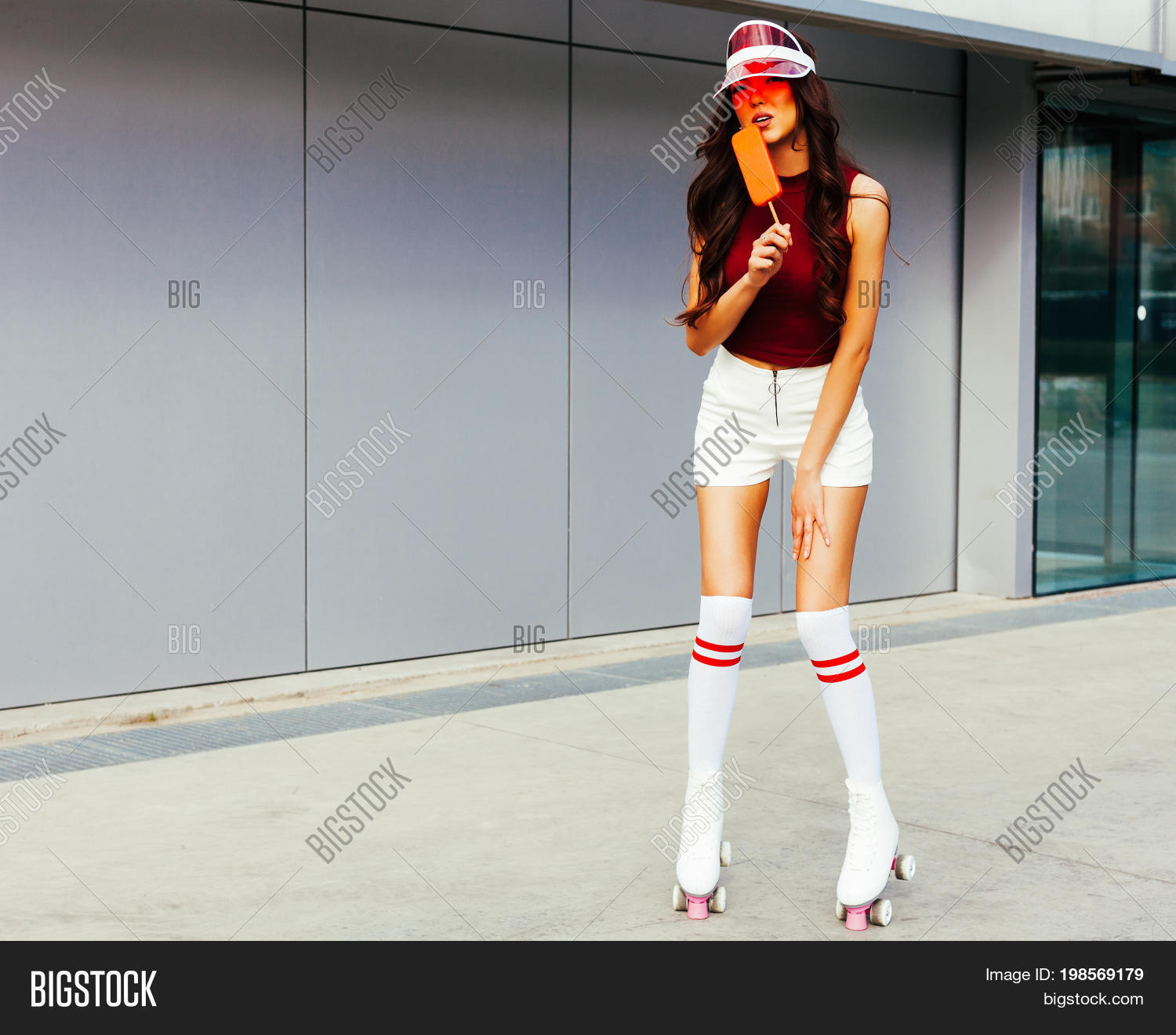 6d206318 Sunny portrait of an long haired leggy Asian girl in a red top white shorts  fashionable red Brim Visor Hat is enjoyed by ice cream. Outdoor.