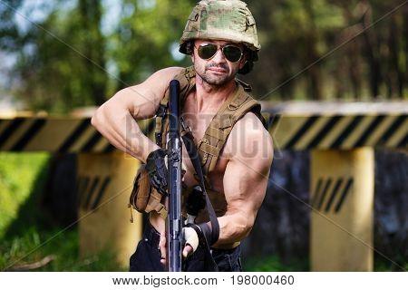 Powerful Mercenary With Submachine Gun Aiming The Target Near Ro