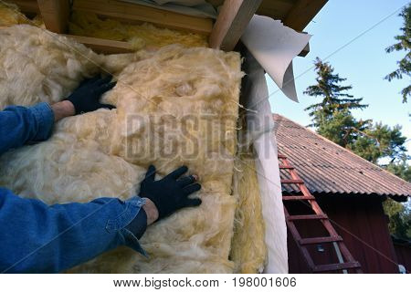 Farmer worker hands insulating with rock wool wooden house wall
