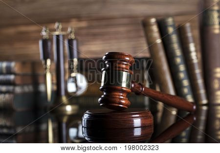 Law and justice concept - gavel of judge and scale of justice and legal code on glass table and wooden background.