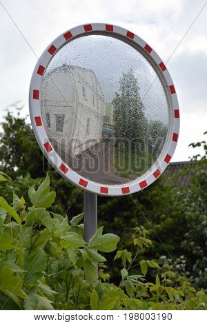 Dewy wet circle street mirror in city after rain
