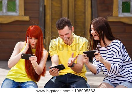 Group Of Three Friends Play Mobile Video Game Outdoors, Girl And