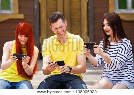 Group Of Three Friends Play Mobile Video Game Outdoors, Girls Wi