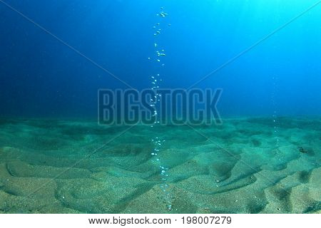 Air bubbles rise through sandy sea bottom. Gas vents underwater