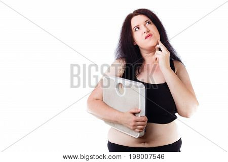 Young Overweight Thoughtful Woman Holding Scale In Hand