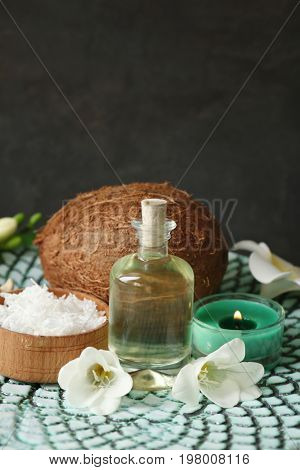 Bottle with oil, desiccated coconut and candle on grey background