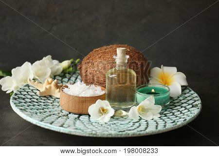 Beautiful spa composition with oil in bottle and coconut on platter