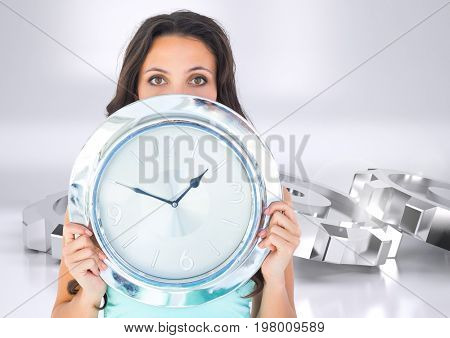 Digital composite of Woman holding chrome clock in front of chrome silver cog wheels