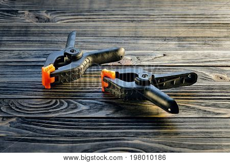 Pair of black clamps with orange plastic jawson on black wood carpenter's bench. Part of the workplace of a carpenter