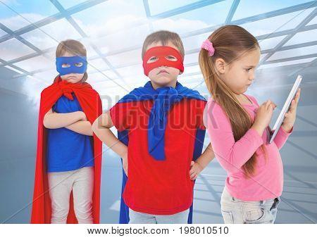 Digital composite of Superhero kids and girl on tablet under windows