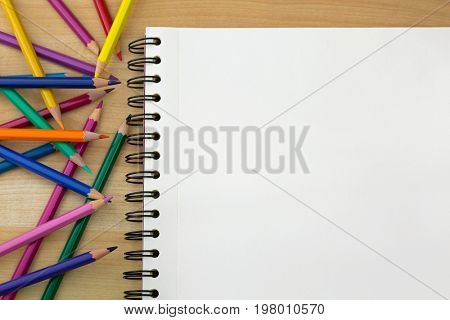 Top view of coloring colored pencils next to sketch drawing book on wooden background