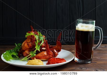Mug Of Dark Beer With Delicious Hot Crusty Grilled Chicken Wings