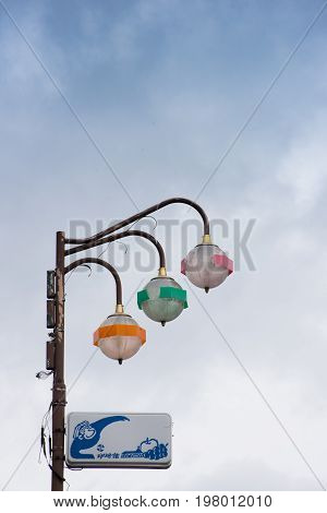 Colorful retro Yudanaka Japan lamp post with orange, green and pink accented fixtures with blue and white sign showing snow monkey and fruit.