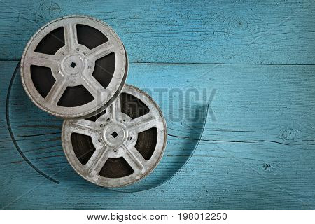 Old film strip on wooden blue background. Top view. Copy space.