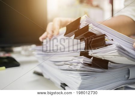 Businessman hands searching information in Stacks of paper files on work desk office business report papers or piles of unfinished documents achieves with clips on offices indoor Business concept poster