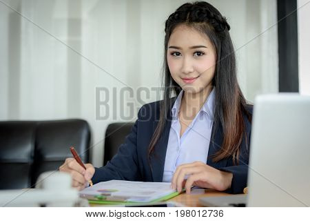 Asian Businesswoman Is Writing And Reading A Paper Report With A Pen Along With A Laptop Computer On