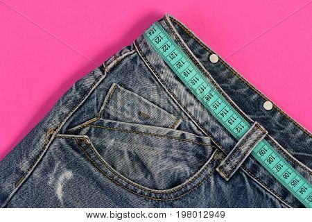 Jeans with blue measure tape instead of belt. Top part of denim trousers isolated on blue background. Close up of jeans belt loops and pocket. Healthy lifestyle and dieting concept.