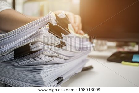 Businessman hands searching information in Stacks of paper files on work desk office business report papers or piles of unfinished documents achieves with clips on offices indoor Business concept