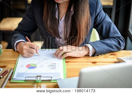 Asian Business Women Are Reading And Writing Trading Reports.