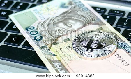 Bitcoin on Nigerian Naira banknote. Electronic money exchange concept