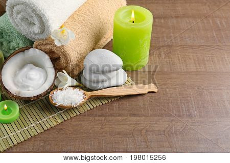 Beautiful spa composition with desiccated coconut in spoon and stones on bamboo mat