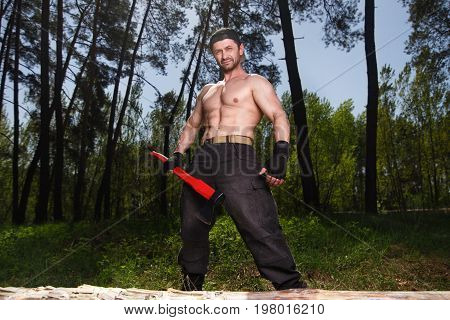 Lumberjack Worker Standing In The Forest With Axe