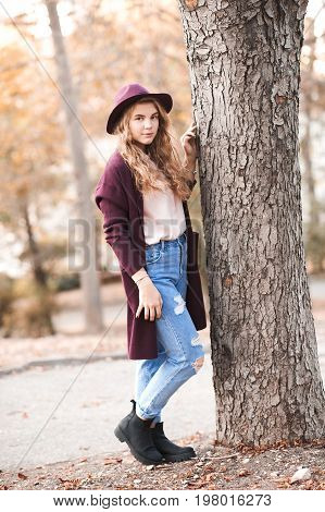 Stylish teen girl 14-16 year old wearing winter jacket hat and denim pants in park.Looking at camera. Childhood.