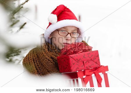 small boy or cute nerd kid in glasses hat and fashionable knitted scarf holds red christmas or new year present boxes in winter outdoor at fir tree with white snow on natural background