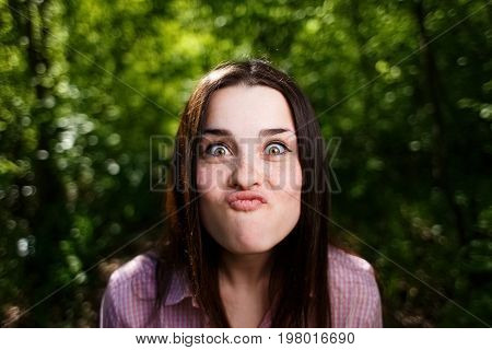 Portrait Of Cute Young Woman Blowing Lips Kiss, Grimacing For Fu