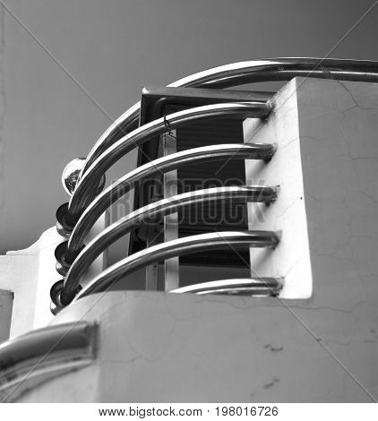 BLACK AND WHITE PHOTO OF CURVING STAINLESS STEEL HANDRAIL