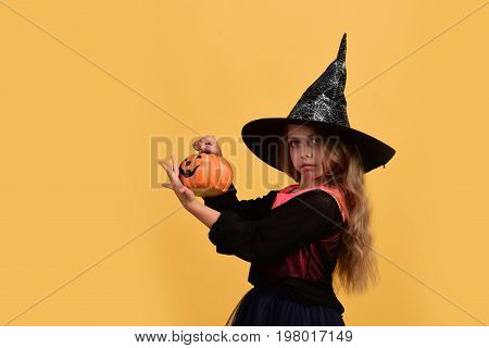 Girl With Carved Orange Pumpkin Isolated On Warm Yellow Background