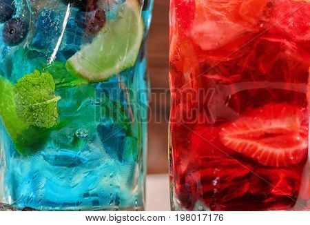 Close-up picture of blue and red drinks. Two alcohol summer cocktails with mint leaves cut strawberries and ice in highball transparent glasses on the wooden background. Cocktails for parties.