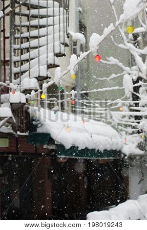 Snowing in Istanbul - closeup of falling snow with colorful lamps on the background