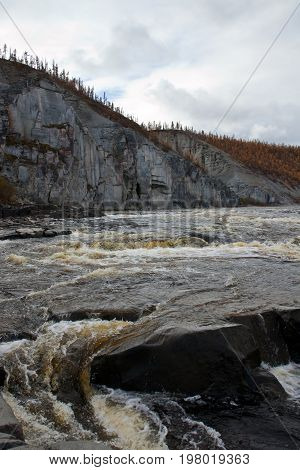 Water threshold on the Siberian taiga river in the fall. Riverbed Moiyero in September during the rafting and fishing for Siberian taimen. Waterfall water threshold Evenkia Krasnoyarsk region Russia
