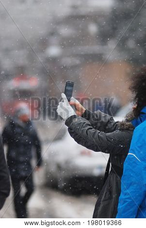 Fragment of a hand holding mobile phone, person taking selfie in winter outside