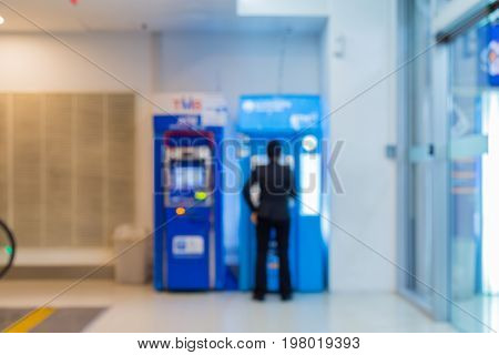 Blurly abstract Female employees are transacting at ATMs.