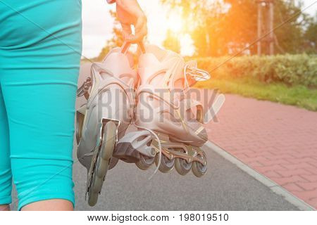 Woman holding roller skates in her hands