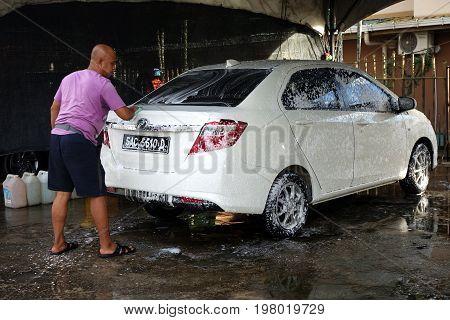 KOTA KINABALU MALAYSIA- 29 JUN 2017: Worker washing the sedan car at the local service car wash.
