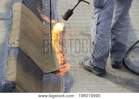 Worker Heating And Melting Bitumen Felt