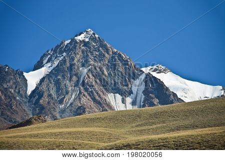 Mountain cliffs glaciers and snowfields in the Tien Shan. View of the top of a ridge in the mountains of Kyrgyzstan in autumn.
