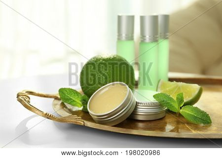 Tray with perfumes, limes and mint leaves on table