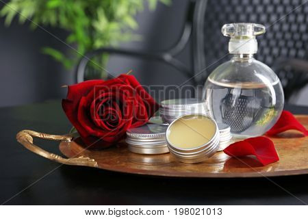 Tray with perfume bottle, containers and rose on dark table