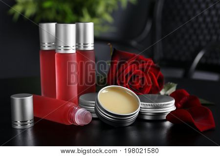 Bottles, containers with perfume and rose on dark table